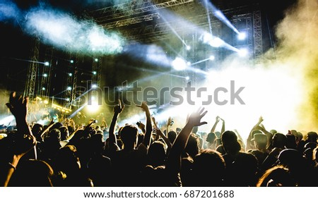 Young people dancing and having fun in summer festival party outdoor - Crowd with hands up celebrating fest concert event - Soft focus on center bottom hand with background flare - Contrast filter Royalty-Free Stock Photo #687201688
