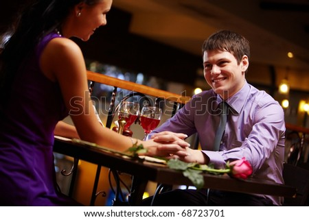 Portrait of amorous couple holding by hands in the cafe #68723701