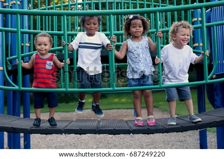 A diverse group of four children are playing together at the park. They are laughing and jumping on a gym. The children are of different races, including African American, Caucasian and Hispanic. #687249220