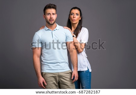 A beautiful young couple standing and feeling scared in a studio #687282187