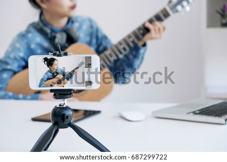 social media learning concept, relaxing and playing guitar, Young woman concentrating learn and play the guitar to a tutorial on lesson online, while she recording music video in camera at home. #687299722