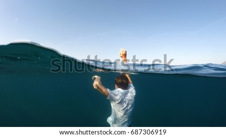 young man sinking into the sea #687306919