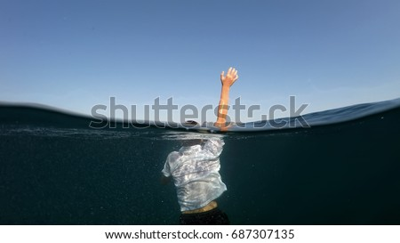 young man sinking into the sea #687307135