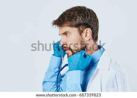 Doctor with a beard with a stethoscope on a light background medicine. #687339823