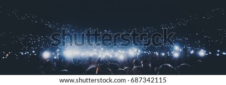 Group of people holding cigarette lighters and mobile phones at a concert  crowd of people silhouettes with their hands up. Dark background, smoke, spotlights. Bright lights #687342115