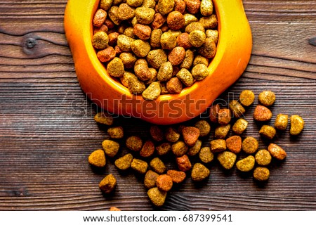 dry cat food in bowl on wooden background top view #687399541