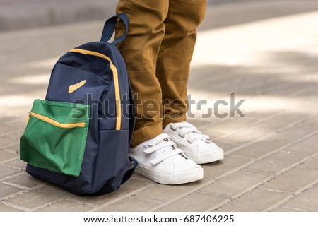 cropped shot of stylish schoolboy standing with backpack on street Royalty-Free Stock Photo #687406225