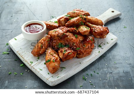 Baked chicken wings with sesame seeds and sweet chili sauce on white wooden board. Royalty-Free Stock Photo #687437104