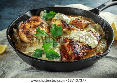Creamy chicken fellets supremes in mushroom sauce with parsley In rustic cast iron skillet. #687437377