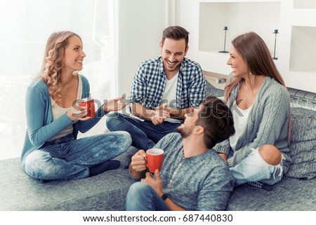 Group of friends talking and having fun while sitting on the couch.They are meet at friend's home for a coffee break. #687440830