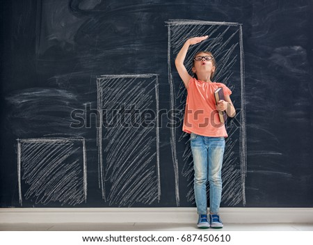 Cute child is playing. Kid measures the growth on the background of blackboard. Concept of education. Royalty-Free Stock Photo #687450610