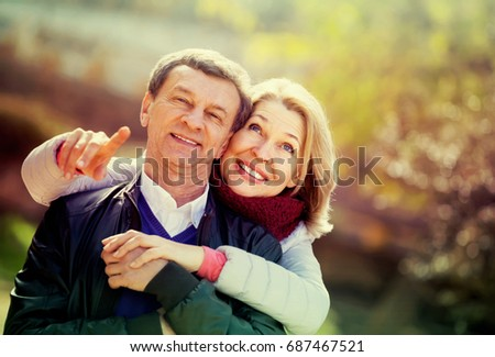 Portrait of smiling mature spouses enjoying spending time at spring park. Focus on woman #687467521