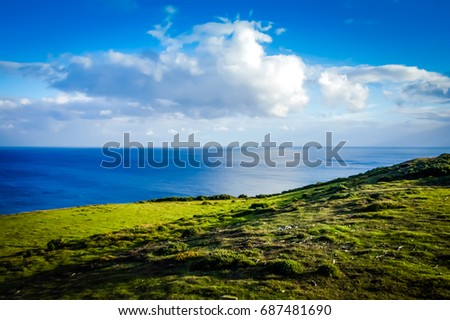 Dramatic landscape with blue sea view. Rural landscape fresh green meadows on a sunny day with blue sky and clouds in springtime. colorful luminous landscape inspirational fantastic nature background #687481690
