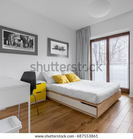 White, multifunctional bedroom with desk, double bed and big balcony door #687553861