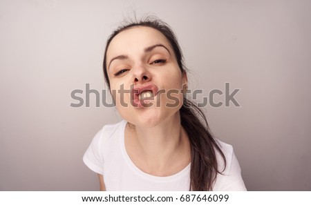 The woman bit her lip on the gray background. #687646099