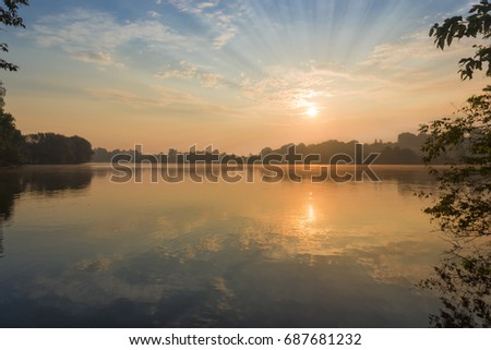 Sun and sky with clouds reflected in water of the pond, on a shores of which grow trees at sunrise   #687681232