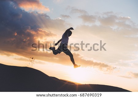 Silhouette of an extreme sportsman engaged in outdoor sports at sunset. Athlete jumping over the ravine. Intentional dark colors #687690319