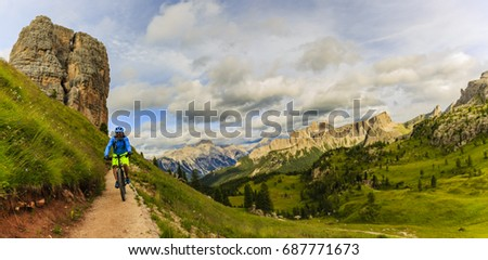 View of cyclist riding mountain bike on single trail in Dolomites, Cinque Torri, South Tirol, Italy #687771673