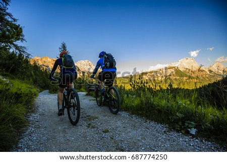 Mountain biking couple with bikes on track at sunset, Cortina d'Ampezzo, Dolomites, Italy #687774250