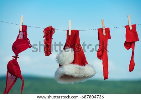 New year costume on blue sky. Laundry and dry cleaning. santa clothes for drying. Xmas red costume on rope with pin. Christmas clothes outdoor. #687804736