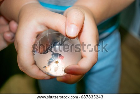 A child is holding the translucent earth ball #687835243