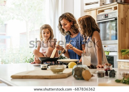 Little sisters cooking with her mother in the kitchen. Infant Chef Concept. Royalty-Free Stock Photo #687836362