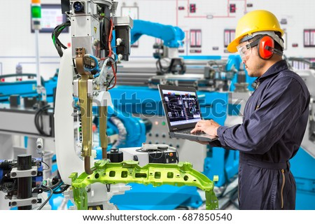 Engineer using laptop computer maintenance automatic robotic hand machine tool in automotive industry manufacturing factory Royalty-Free Stock Photo #687850540
