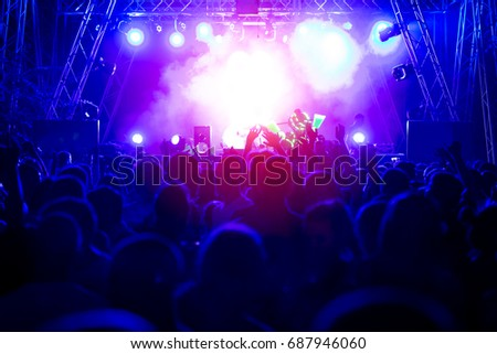 Silhouettes of concert crowd in front of bright stage lights #687946060