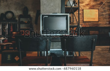 Blank space of monitor screen on vintage cafe background and retro black metal chair, use to put movie on blank screen