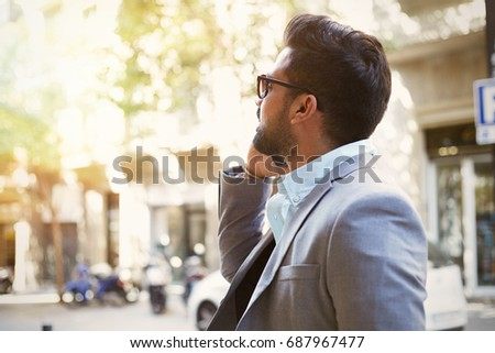Young businessman talking on his phone outdoors and wearing buseness suit #687967477