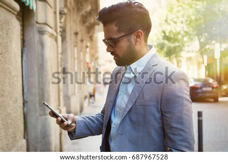 Young businessman talking on his phone outdoors and wearing buseness suit #687967528