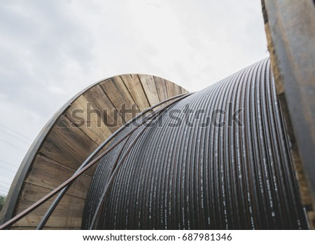 black wire  electric cable with wooden coil of electric cable under the sky. #687981346