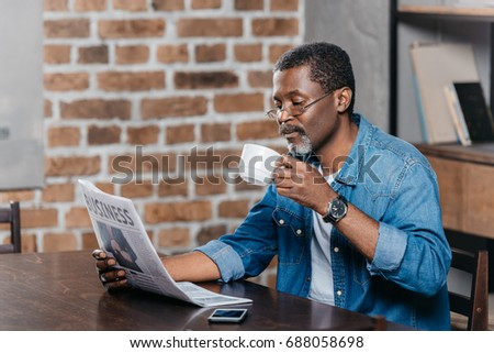 African american man reading newspaper and having coffee at table #688058698