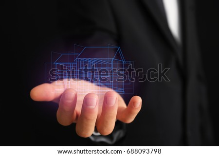Real estate agent holding projection of house on dark background #688093798