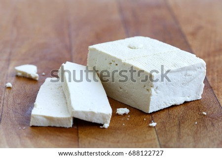 Single block of white tofu and two tofu slices with crumbs on wooden chopping board. #688122727