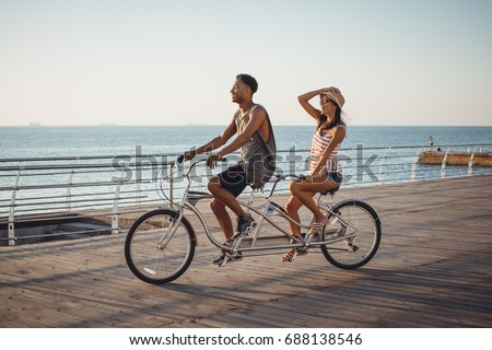 Portrait of a mixed race couple riding on tandem bicycle outdoors near the sea #688138546