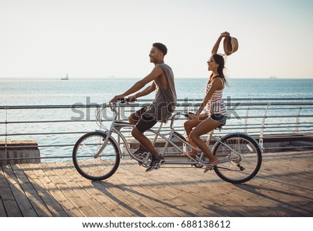 Portrait of a mixed race couple riding on tandem bicycle outdoors near the sea #688138612