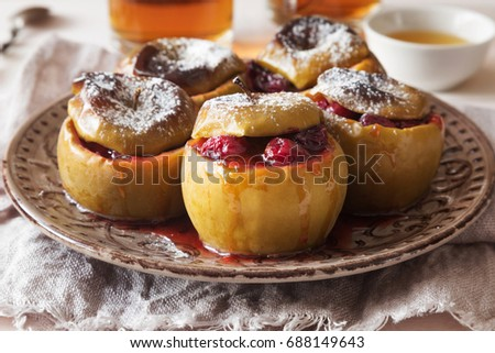 Horizontal photo of baked apples with cranberry and sugar powder #688149643