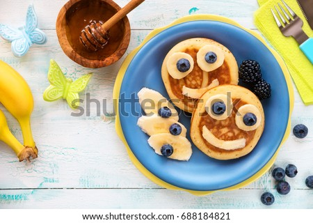Fun food for kids - cute smiling faces on sweet pancakes for breakfast with bananas, fresh blueberries and blackberries. Creative cooking for children #688184821