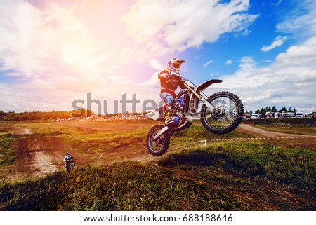 racer on mountain bike participates in  race, takes off and jumps on springboard, against the background of the participants. Close-up. concept of extreme rest, sports racing. ray of light