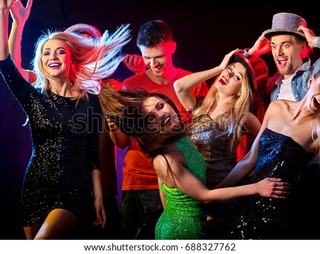 Dance party with group people dancing. Women and men have fun in night club. Happy girl with tousled hair on foreground. Back light on girls hair. Rest after a hard day at work. #688327762