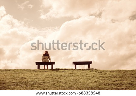 a women sitting alone on a bench waiting for love, alone concept Royalty-Free Stock Photo #688358548