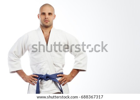 A young strong man in a white kimono for sambo, jiu jitsu and other martial arts with a blue belt posing on white isolated background, hands holding on his belt Royalty-Free Stock Photo #688367317