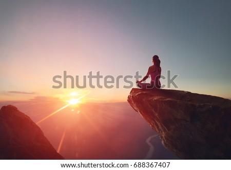 Woman practices yoga and meditates on the mountain. Royalty-Free Stock Photo #688367407