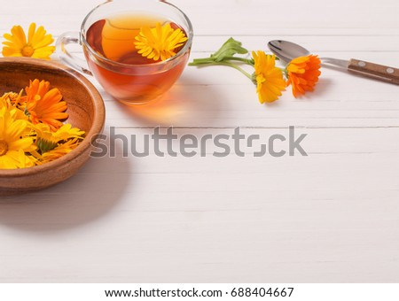 Calendula (Marigold) herbal tea  on white wooden table #688404667