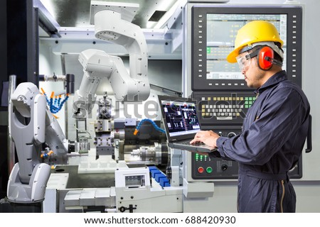 Engineer using laptop computer for maintenance automatic robotic industrial with CNC machine in smart factory. Industry 4.0 concept #688420930