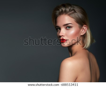 Beautiful young girl in studio on gray background. Close-up portrait. Hairstyle styling.Fashion, beauty, make-up, cosmetics, beauty salon, haircut, hairstyle, self-care, health.Smooth tanned skin.