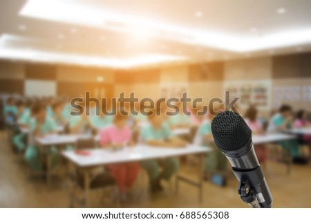 Microphone over the Abstract blurred photo of conference hall or seminar room with attendee background,training new worker in factory. #688565308