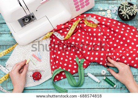 flat lay with tailor holding pins and bobbin in hands at workplace with textiles and tailoring items on wooden table #688574818
