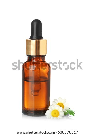 Bottle of essential oil and chamomile flowers on white background #688578517